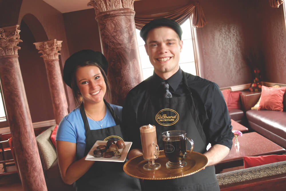 DeBrand Chocolate employees holding chocolate products.